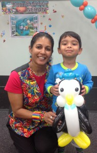 Child with a penguin balloon sculpture